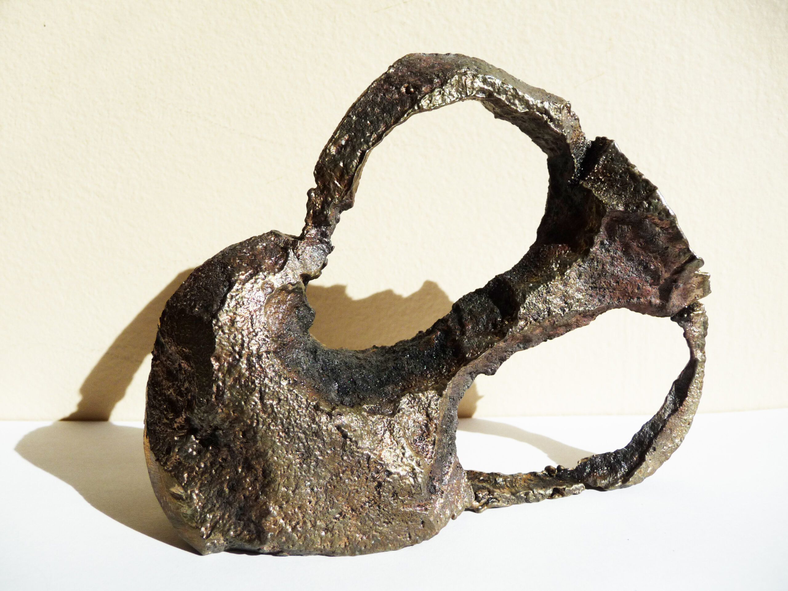 Small bronze sculpture shaped like an abstract vase by artist Carrie Ruddick.